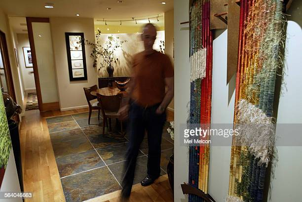 Al Rosen walks towards hallway next to dining room of his home in Brentwood Dining room floor is a combination of certified cherry wood and slate...
