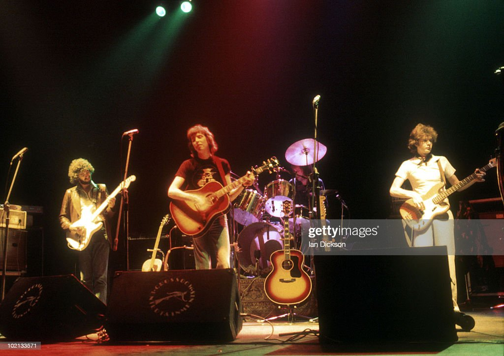 Al Stewart (centre) performs live on stage at Hammersmith Odeon in London in November 1976
