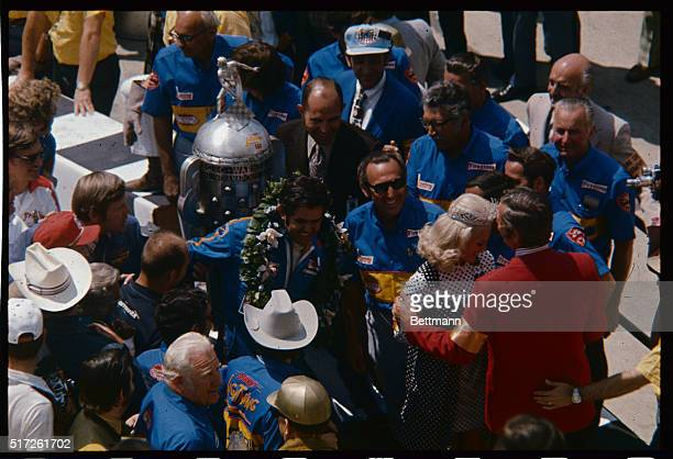 Al Unser of Albuquerque New Mexico wearing wreath is surrounded by cheering crowd in winner's circle at Indianapolis Speedway after he won...