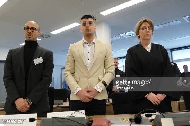 Alaa S stands with a translator and Ricarda Lang one of his lawyers as he arrives in court for the first day of his trial for the possible murder of...