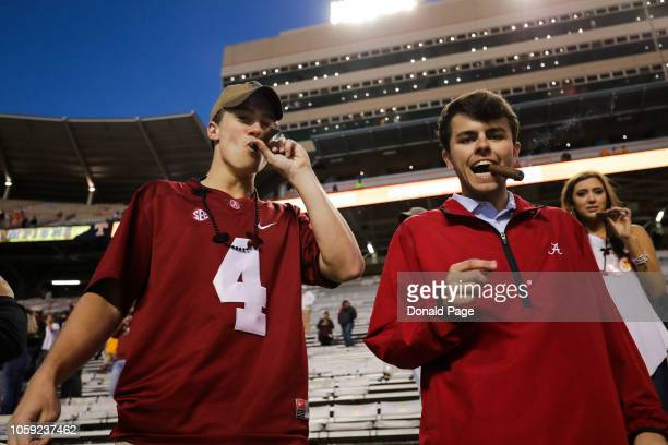 Alabama Crimson Tide fans smoke a celebratory cigar after the Tide wins the game between the Alabama Crimson Tide and the Tennessee Volunteers at...