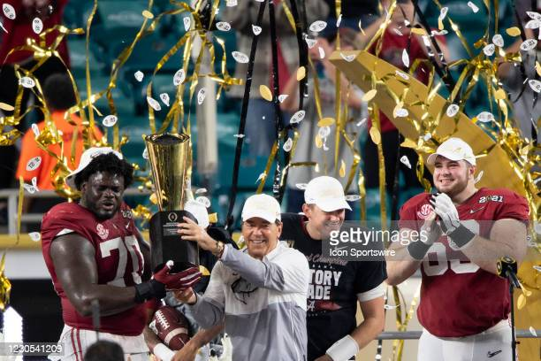 Alabama Crimson Tide offensive lineman Alex Leatherwood and Alabama Crimson Tide head coach Nick Saban hold the trophy as they celebrate on the stage...