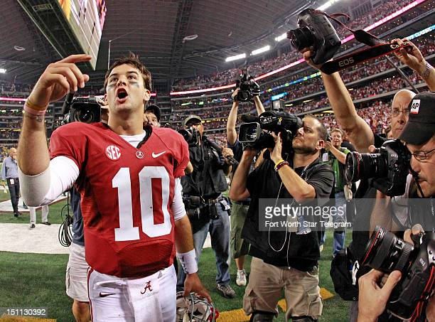 Alabama Crimson Tide quarterback AJ McCarron yells up at his family in the stands following a 4114 victory over Michigan in the Cowboys Classic at...
