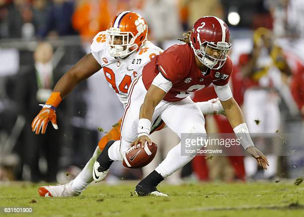 Alabama Crimson Tide quarterback Jalen Hurts avoids a tackle by Clemson Tigers defensive tackle Carlos Watkins and rushes in for a touchdown late in...
