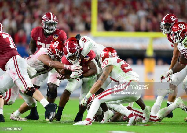Alabama Crimson Tide running back Josh Jacobs is tackle by Oklahoma Sooners linebacker Kenneth Murray and Sooners defensive end Amani Bledsoe during...