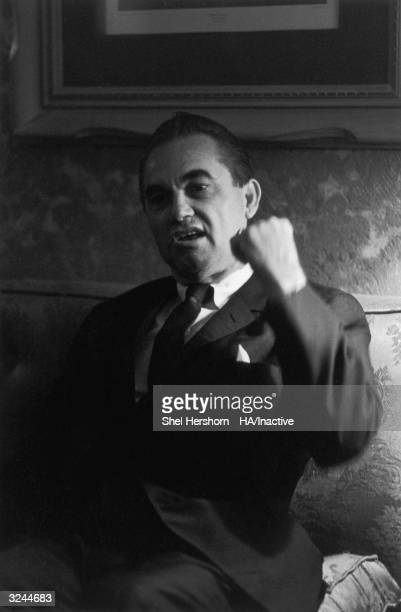 Alabama governor George Wallace raises his fist as he sits on a sofa and speaks while attending the Democratic National Convention in Chicago...