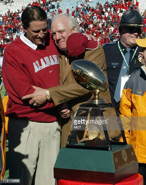 Alabama head coach Mike Shula left hugs athletic director Mal Moore before being presented with the Cotton Bowl trophy after their 1310 win against...