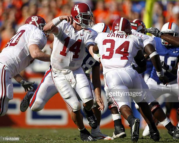 Alabama quarterback John Parker Wilson makes this handoff to Kenneth Darby during Saturday's contest at Ben Hill Griffin Stadium in Gainesville...