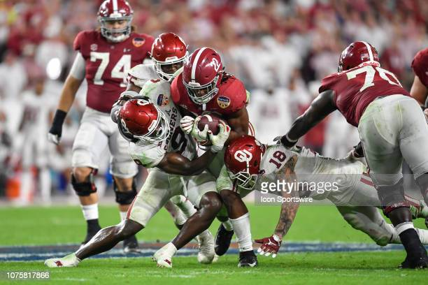 Alabama running back Najee Harris is tackled by Oklahoma linebacker Kenneth Murray and Oklahoma linebacker Curtis Bolton during the second half of...