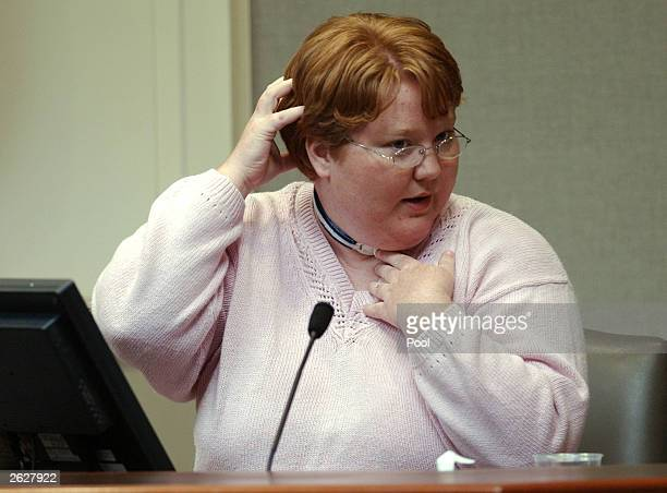 Alabama sniper victim Kellie Adams demonstrates how a bullet entered the back of her head and exited her chin during her testimony in the murder...