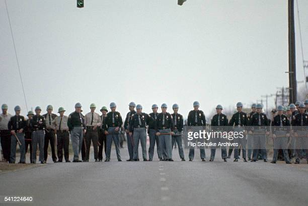 Alabama state highway patrol officers line up across a road to block a civil rights march from leaving Selma