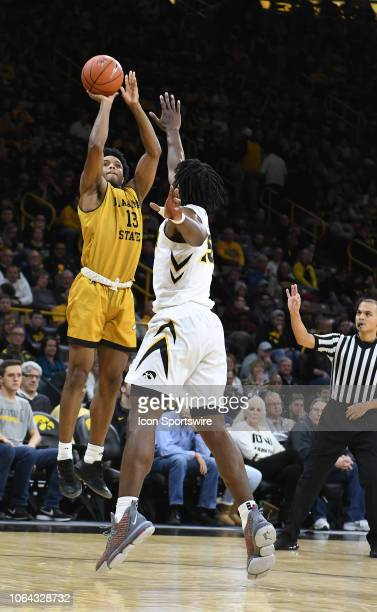 Alabama State Hornets forward AJ Farrar puts up a shot over Iowa Hawkeyes forward Tyler Cook during a nonconference basketball game between the...
