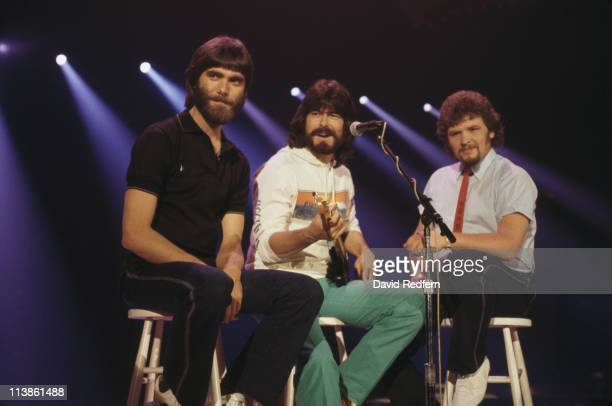 Alabama US country music band pose sitting on stools circa 1980