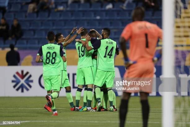 AlAhli's defender Ageel AlSahbi is congratulated after scoring his team's opening goal during the AFC Champions League football match between...