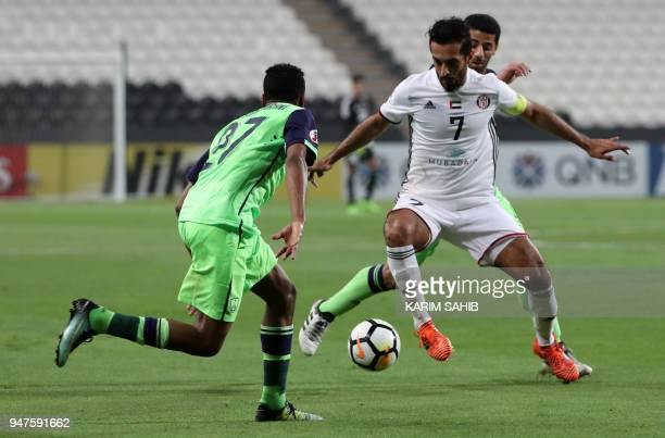AlAhli's defender Hamdan AlShamrani vies for the ball with AlJazira's forward Ali Mabkhout during their AFC Champions League match between Emirates'...