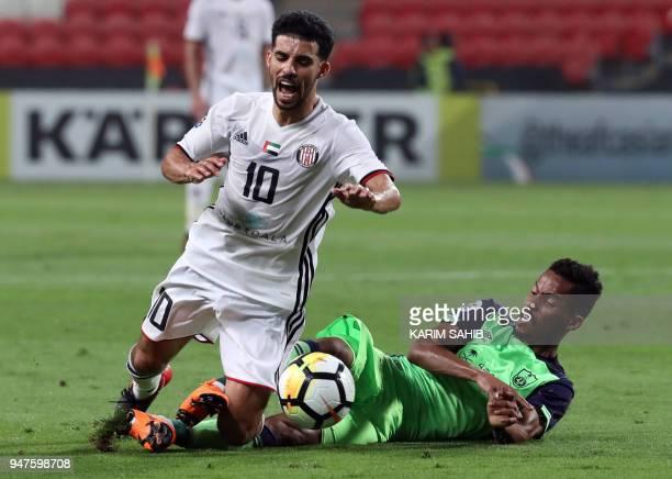 AlAhli's defender Hamdan AlShamrani vies for the ball with AlJazira's midfielder Mbark Boussoufa during their AFC Champions League match between...