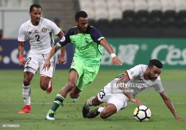AlAhli's defender Hamdan AlShamrani vies for the ball with AlJazira's midfielder Harib AlSaadi during their AFC Champions League match between...