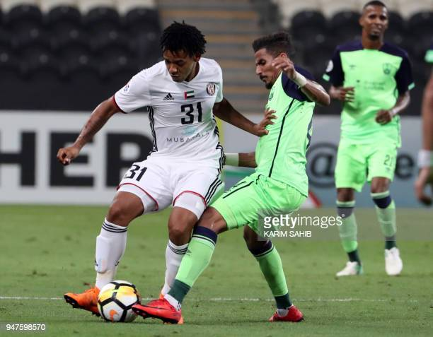 AlAhli's defender Waleed Bakshween vies for the ball with AlJazira's forward Romarinho during their AFC Champions League match between Emirates'...