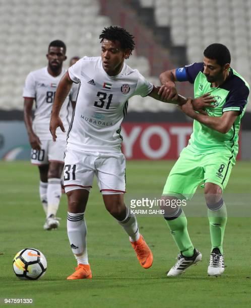 AlAhli's midfielde rand captain Taisir AlJassim vies for the ball with AlJazira's forward Romarinho during their AFC Champions League match between...