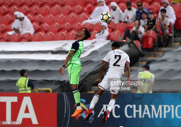 AlAhli's midfielder Salman AlMoasher vies for the ball with AlJazira's defender Mohamed Fawzi during their AFC Champions League match between...