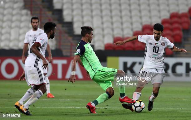 AlAhli's midfielder Salman AlMoasher vies for the ball with AlJazira's midfielder Mbark Boussoufa during their AFC Champions League match between...