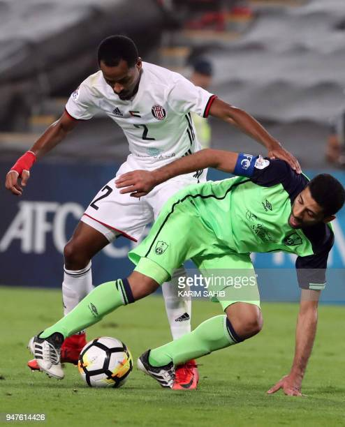 AlAhli's midfielder Taisir AlJassim vies for the ball with AlJazira's defender Mohamed Fawzi during their AFC Champions League match between...