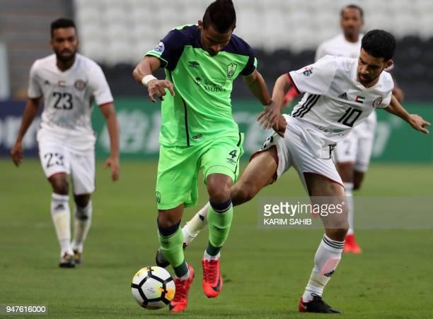 AlAhli's midfielder Waleed Bakshween vies for the ball with AlJazira's midfielder Mbark Boussoufa during their AFC Champions League match between...