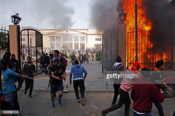 AlAhly club supporters run away from smoke and flames rising from the police officers' club in Cairo on March 9 after several buildings in the...