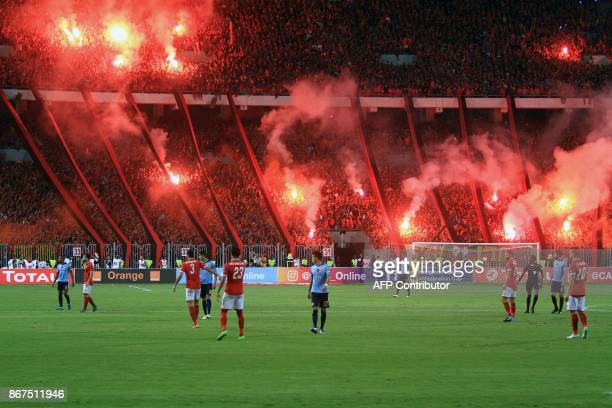 AlAhly supporters carry flares during the CAF Champions League final football match between AlAhly vs Wydad Casablanca at the Borg El Arab Stadium in...
