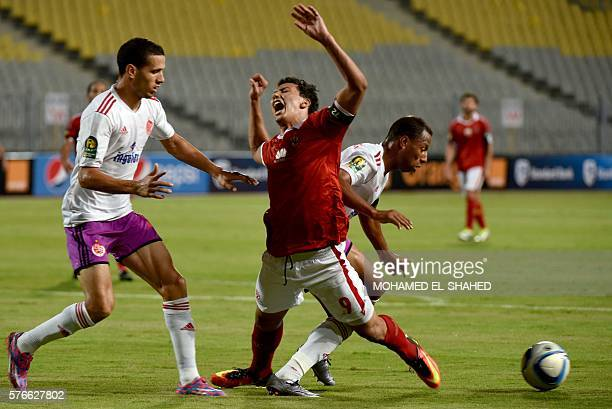 AlAhly's Amr Gamal reacts as he is dispossessed by Wydad's Brahim Nakach and Abdellatif Noussir during their CAF Champions League group A stage...