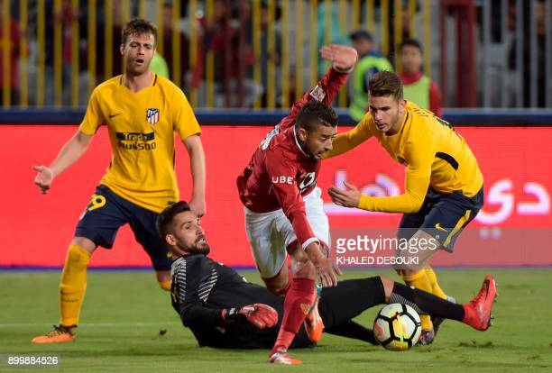 AlAhly's Basem Ali vies for the ball with Atletico Madrid's Spanish goalkeeper Miguel Angel Moya during the friendly football match between Egypts...