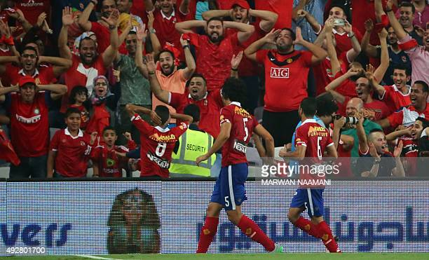 AlAhly's Momen Zakrya celbrates with supporters and teammates after scoring his team's third goal during the Egypt super cup football match between...