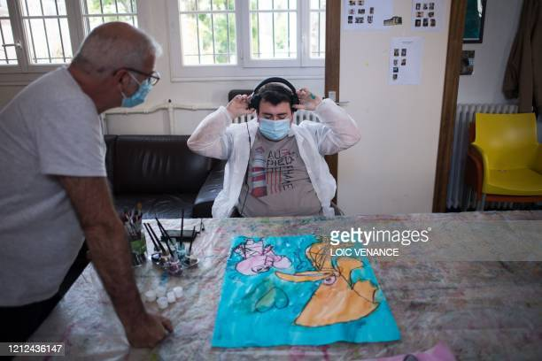 """Alain , an educator and art therapist, works with """"Yago"""", a young autistic man hosted at the Santos-Dumont day mental hospital of the """"Elan Retrouve""""..."""