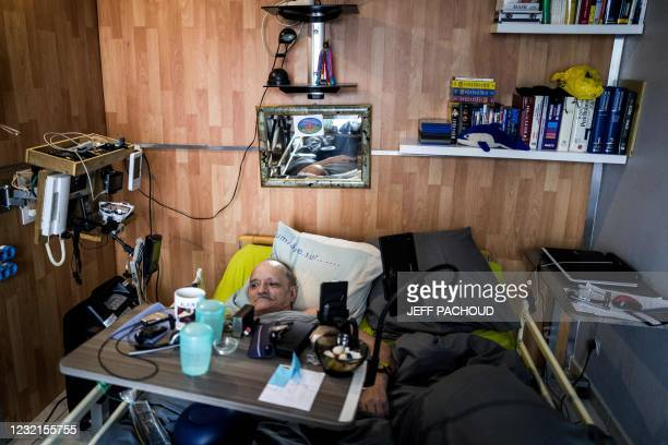Alain Cocq, suffering from an incurable orphan disease, touches his phone in his medical bed at his home in Dijon on April 6, 2021. - French National...