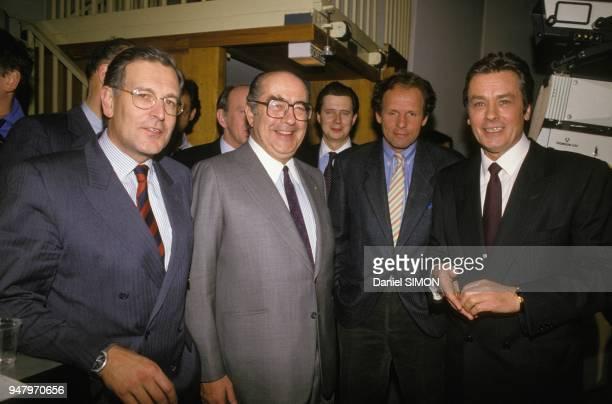 Alain Delon avec Patrick Le Lay Francis Bouygues et Patrick Poivre d'Arvor lors de sa venue a TF1 le 14 mars 1988 a Paris France
