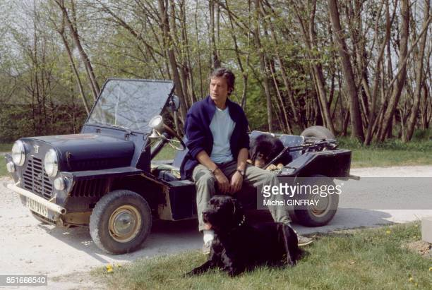 Alain Delon avec sa Mini Moke et son chien chez lui à Douchy le 9 avril 1980 France