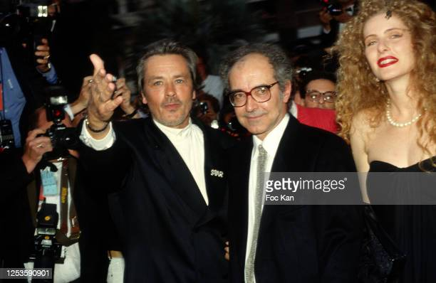 Alain Delon, director Jean Luc Godard and actress Domiziana Giordano attend the 43th Cannes film Festival in May 1990, in Cannes, France.