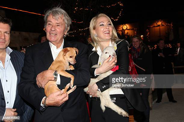 Alain Delon with dog and Kathrin Glock with lamb during the Opening of the Gut Aiderbichl Christmas Market on November 11 2014 in Henndorf am...