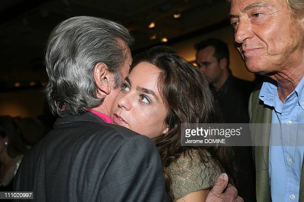 Alain DelonFrench actor Anouchka his daughter and Pierre Cornette de SaintCyr French auctioneer attend a cocktail party at the Hotel DrouotMontaigne...