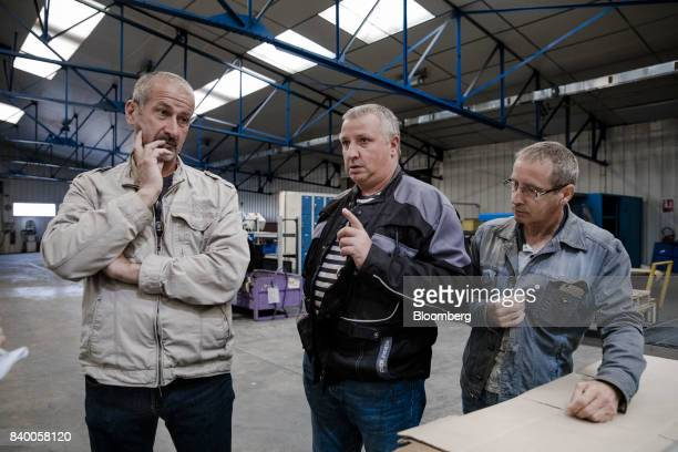 Alain Dubois Bernard Chapoutaud and Philippe Lester workers at GMS automobile parts factory look on during a meeting on the future of their jobs...