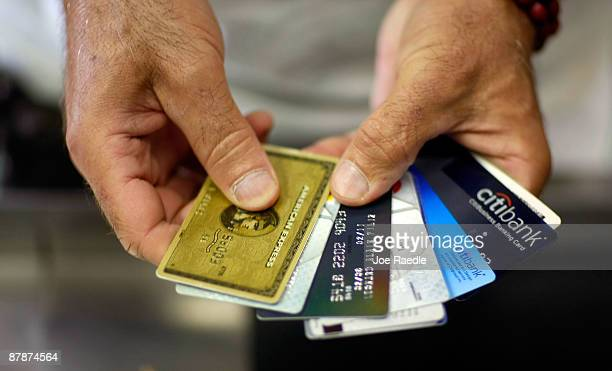 Alain Filiz shows off some of his credit cards as he pays for items at Lorenzo's Italian Market on May 20 2009 in Miami Florida Members of Congress...