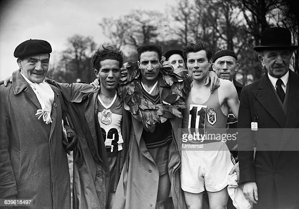 Alain Mimoun from France celebrates his victory in the 1952 International Cross Country Championships Abdelkader Driss of France came in third and...
