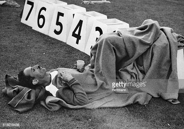 Alain Mimoun of France first place winner of the Olympic marathon event butts his feet against the number one position stand and nurses a drink after...
