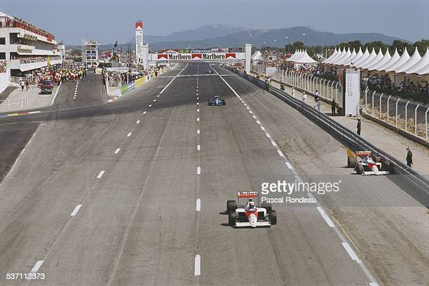 Alain Prost drives the Marlboro McLaren Honda MP4/5 past the retired car of team mate Ayrton Senna during the French Grand Prix on 9 July 1989 at the...