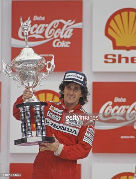 Alain Prost of France driver of the Honda Marlboro McLaren McLaren MP4/4 Honda V6 turbo celebrates with the trophy after winning the Brazilian Grand...