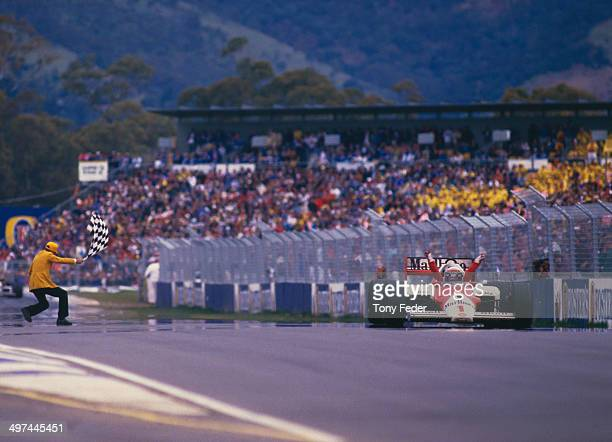Alain Prost of France in the Marlboro McLaren International McLaren MP4/2C TAG V8 turbo takes the chequered flag to win the Australian Grand Prix at...