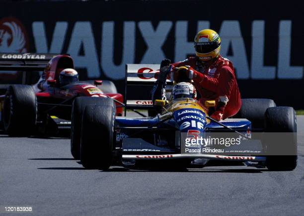 Alain Prost watches from behind as Nigel Mansell driving the Canon Williams Renault Williams FW14 Renault 35 V10 gives Ayrton Senna a ride back to...