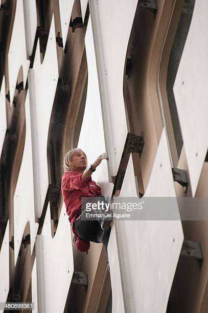 Alain Robert climbs the Ariane Tower situated in the La Defense business centre on March 27 2014 in Paris France After taking approximately 45...