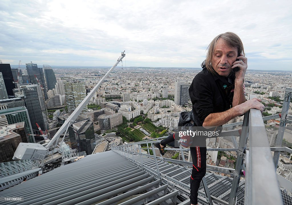 Alain Robert, known as the French 'Spiderman', uses his mobile phone after climbing the 231-meter high First Tower, the tallest skyscraper in France, at La Defense district in Courbevoie, outside Paris on May 10, 2012. Robert has climbed more than 100 of the world's tallest buildings, including the 828-metre Burj Khalifa in Dubai, Petronas Twin Towers in Kuala Lumpur, Sears Tower in the US city of Chicago and the 88-storey Jin Mao Building in Shanghai, China.