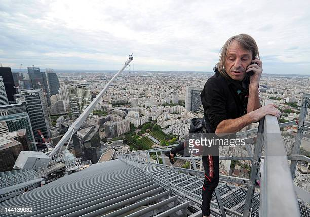 Alain Robert known as the French 'Spiderman' uses his mobile phone after climbing the 231meter high First Tower the tallest skyscraper in France at...